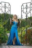 Frau im blauen Kleid, das am Metalltor steht Stockfoto