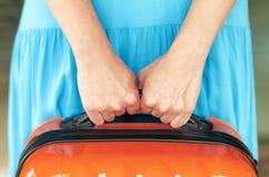 Frau im blauen Kleid hält orange Koffer in den Händen Stockfotos