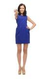 Frau im blauen Kleid ihren Finger zeigend Stockfoto