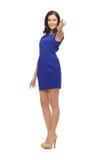 Frau im blauen Kleid ihren Finger zeigend Stockbild