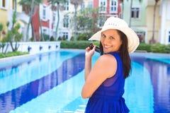 Frau im blauen Kleid und im weißen Hut lächelnd durch den Swimmingpool Stockfoto
