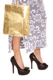 Frau im blauen Rock folgt Goldtasche auf den Fersen Stockbilder