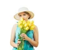 Frau im blauen Sommerkleid mit einem Blumenstrauß von den gelben Tulpen lokalisiert auf einem weißen Hintergrund Stockbild