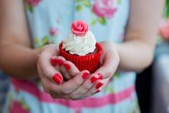 Frau im Blumenkleid mit den gemalten Nägeln, die hübschen kleinen Kuchen halten Lizenzfreie Stockfotos
