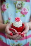 Frau im Blumenkleid mit den gemalten Nägeln, die rosafarbenen kleinen Kuchen halten Stockfotos