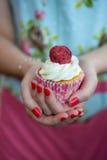 Frau im Blumenkleid mit den gemalten Nägeln, die verziertes cupca halten Stockbild