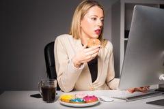 Frau im Büro ungesunde Fertigkost essend Stockfotografie