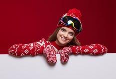 Frau im bunten Hut und Handschuhe, die von hinten whiteboard lugen stockfotografie