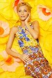 Frau im bunten Kleid, das unter Blumen liegt Stockbild