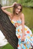 Frau im bunten Kleid des Sommers, das auf Baum legt Stockfotos