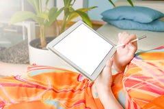 Frau im bunten Kleid in einem Wohnzimmer mit einem Stift auf die weiße Tablette schreibend stockfotos