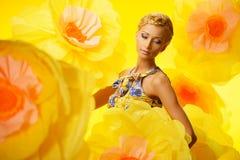 Frau im bunten Kleid unter gelben Blumen Stockbild