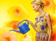 Frau im bunten Kleid unter gelben Blumen Stockbilder