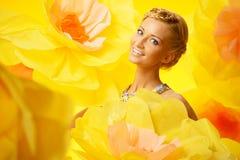 Frau im bunten Kleid unter großen Blumen Lizenzfreie Stockfotos