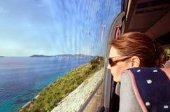 Frau im Bus schaut aus dem Fenster auf einer Seelandschaft heraus Stockbild