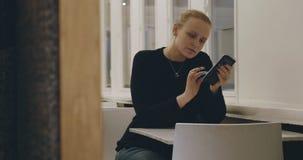 Frau im Café, das auf Mobile simst stock footage