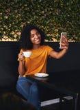 Frau im Café, das selfie auf Smartphone nimmt lizenzfreies stockbild