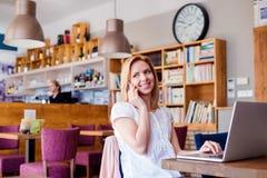 Frau im Café, sprechend am Telefon, das an Notizbuch arbeitet Lizenzfreie Stockbilder
