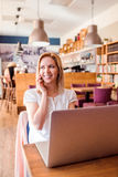 Frau im Café, sprechend am Telefon, das an Notizbuch arbeitet Stockbilder