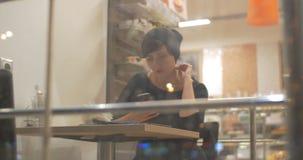 Frau im Café in Verbindung stehend im beweglichen on-line-Boten stock footage