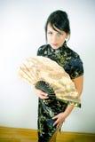Frau im Chinesekleid mit Gebläse Stockbilder