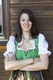 Frau im Dirndl, der an einem Holzhaus sich lehnt Stockfotografie
