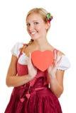 Frau im Dirndl, der rotes Herz hält Stockfotografie