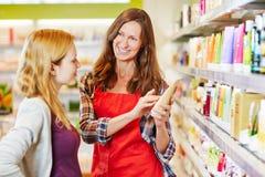 Frau im Drugstore erhält Rat von der Verkäuferin Stockbild