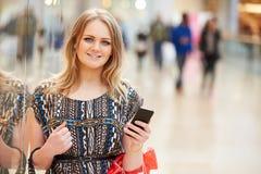 Frau im Einkaufszentrum unter Verwendung des Handys Stockfotos