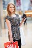 Frau im Einkaufszentrum unter Verwendung des Handys Lizenzfreies Stockbild