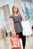 Frau im Einkaufszentrum unter Verwendung des Handys Lizenzfreie Stockfotos