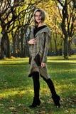 Frau im eleganten Designmantelgehen im Freien gegen eine Herbstnaturlandschaft Lizenzfreies Stockbild