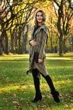 Frau im eleganten Designmantelgehen im Freien gegen eine Herbstnaturlandschaft Stockfotos