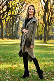 Frau im eleganten Designmantelgehen im Freien gegen eine Herbstnaturlandschaft Stockfotografie