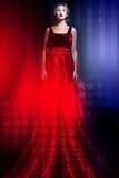 Frau im eleganten roten Kleid mit amerikanischer Flagge Lizenzfreies Stockbild