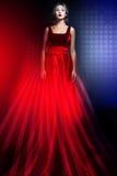 Frau im eleganten roten Kleid mit amerikanischer Flagge Stockfotografie