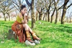 Frau im ethnischen Kostüm sitzt unter den Bäumen stockfotos