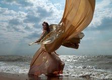Frau im exotischen Kleid, das auf dem Strand steht stockbild