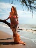 Frau im exotischen Kleid, das auf dem Strand steht lizenzfreies stockfoto