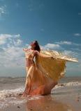 Frau im exotischen Kleid, das auf dem Strand steht Stockfotos