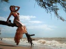 Frau im exotischen Kleid, das auf einem Zweig sitzt Stockbild