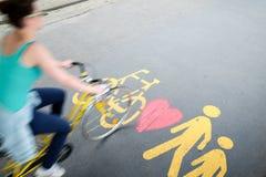 Frau im Fahrrad, das durch das Fußgänger-/Fahrradzeichen überschreitet stockbild