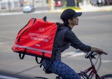 Frau im Fahrrad, das für Rappi-Nahrungsmittelzustelldienst arbeitet lizenzfreie stockfotos