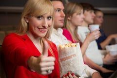Frau im Filmtheater, das sich Daumen zeigt Stockbild