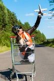 Frau im Fliegersturzhelm auf der Laufkatze mit Spielzeugflugzeug Stockfotografie