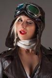 Frau im Fliegersturzhelm blinzelt und Lippen leckend Stockbild