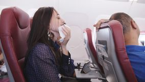 Frau im Flugzeug erbrochen in einer Papiert?te Reisender in einem fliegenden Flugzeug hat Ekel erregendes Übelkeitspassagier in e stock video
