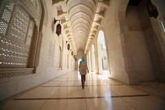 Frau im Flur innerhalb der großartigen Moschee in Oman Lizenzfreies Stockbild