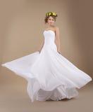 Frau im frühlingshaften Kranz von Blumen im Fliegen-Hochzeits-Kleid Lizenzfreie Stockfotos