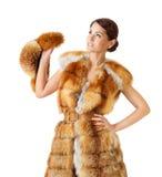 Frau im Fuchspelzmantel, Winterpelzhut halten. Lokalisierter weißer Hintergrund. Lizenzfreies Stockbild